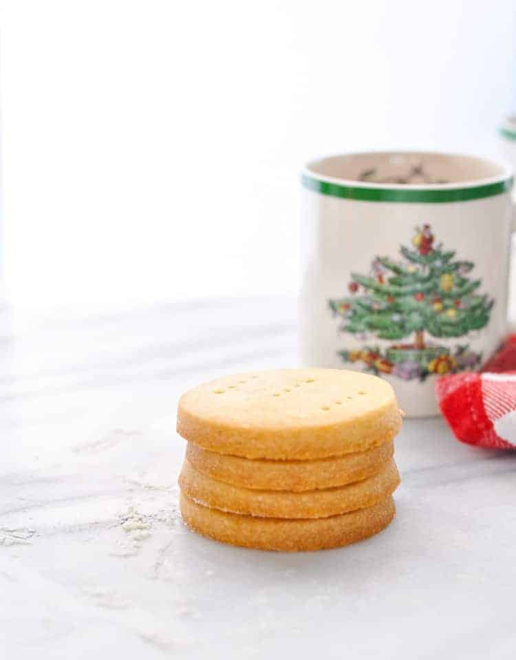 Stack of shortbread cookies on a white marble counter with Christmas mug in background