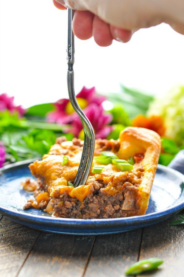 A ground beef casserole on a plate with a fork