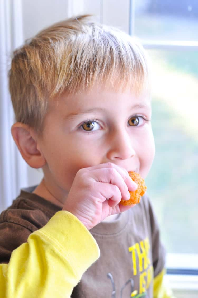 A small boy eating chicken nuggets