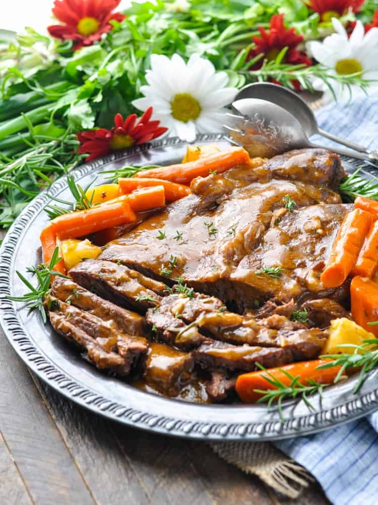 A classic pot roast on a large serving plate with vegetables