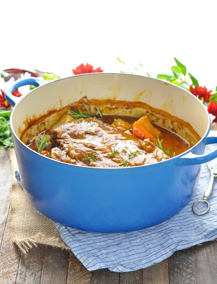 A classic pot roast in a blue pot sitting on a wooden surface