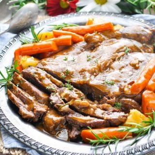 A classic pot roast on a serving plate with veggies