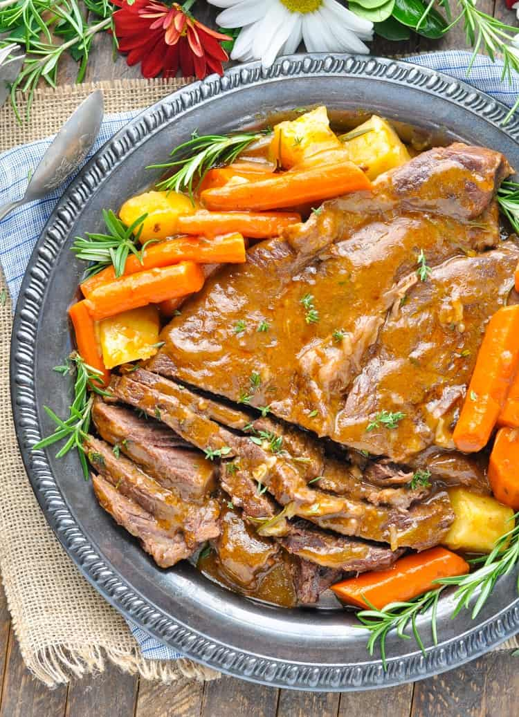An overhead shot of a classic pot roast on a plate with vegetables and rosemary