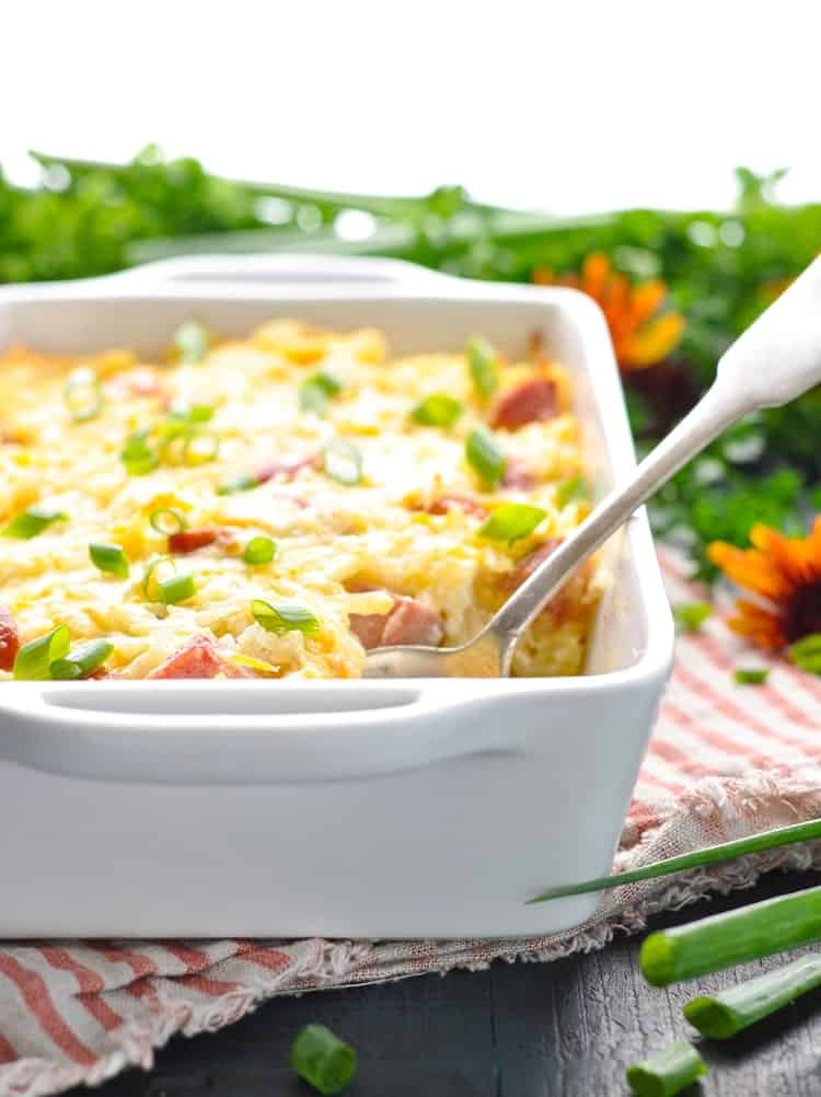 Front view of hash brown breakfast casserole with sausage in white baking dish