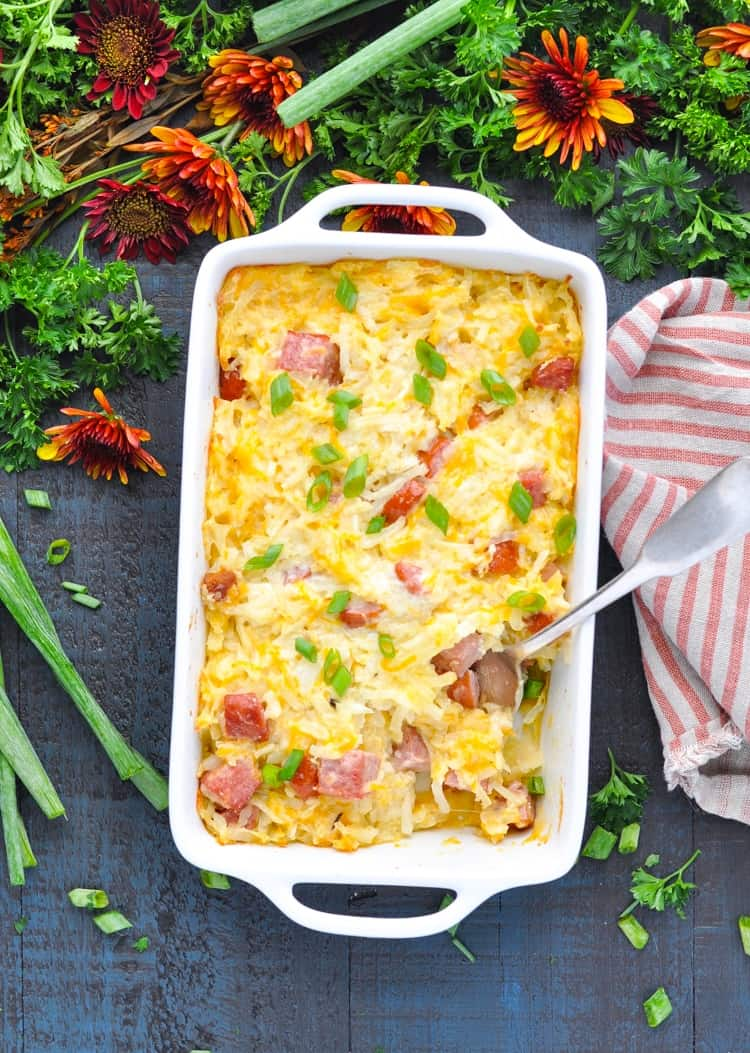 Kielbasa and potato casserole overhead image surrounded by flowers and herbs