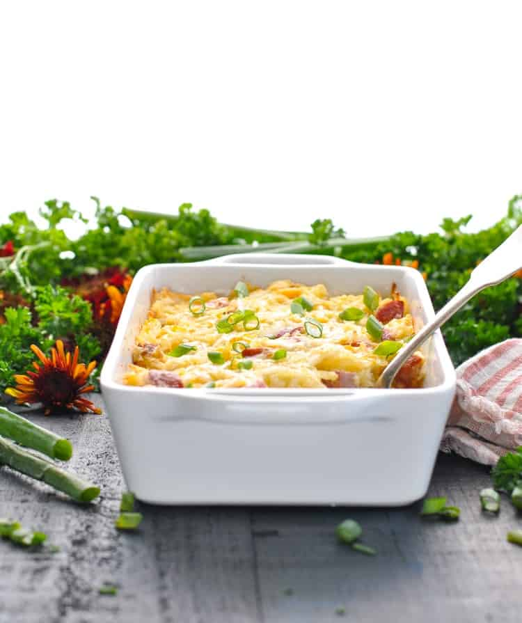 Hash brown and kielbasa sausage casserole in a white dish with serving spoon