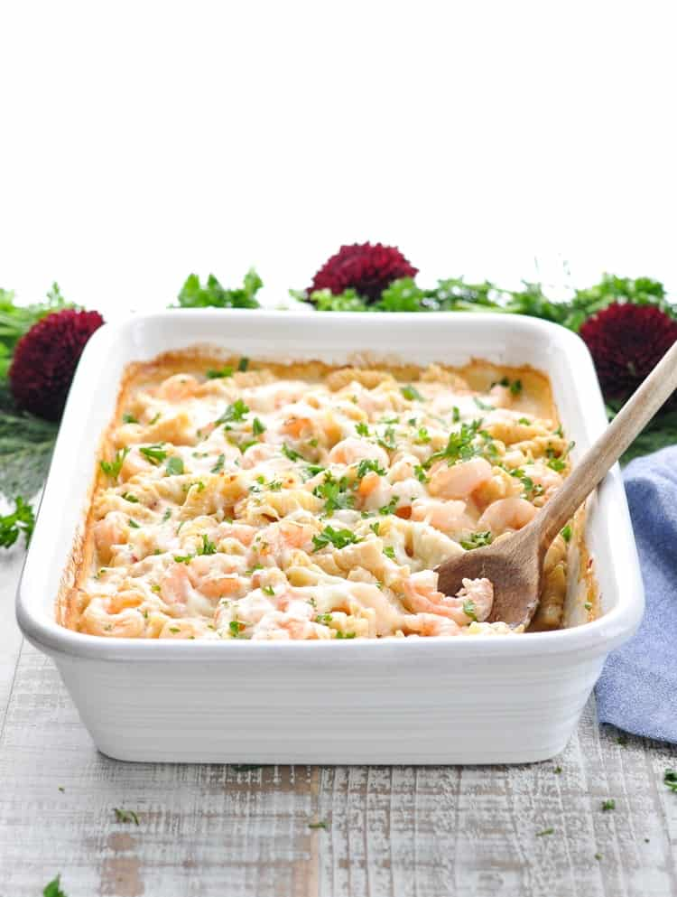 A side shot of a baking casserole dish filled with creamy shrimp pasta