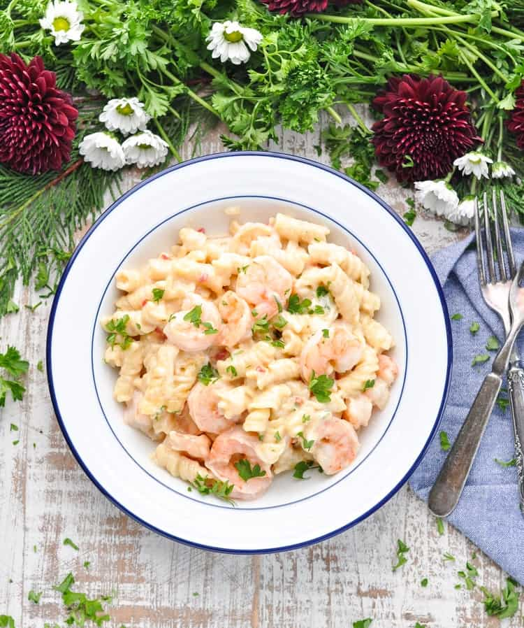 An overhead shot of a white bowl of creamy shrimp pasta topped with parsley