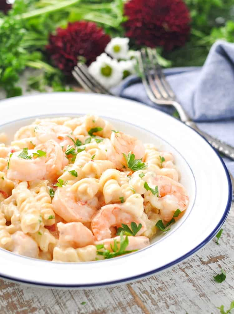 A white bowl of creamy shrimp pasta topped with parsley