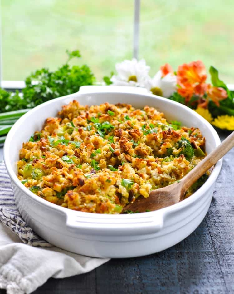 A side shot of a cheesy broccoli casserole in a white dish with a wooden spoon