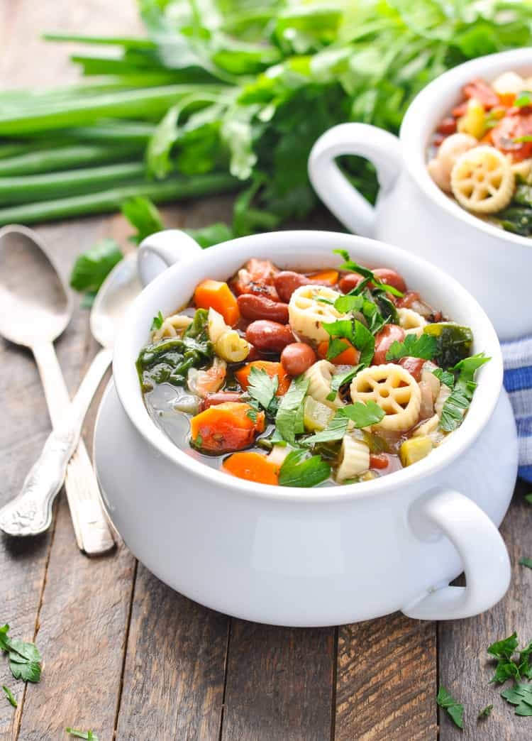 A White Bowl Filled With Homemade Minestrone Soup And Green Herbs In The Background This Recipe
