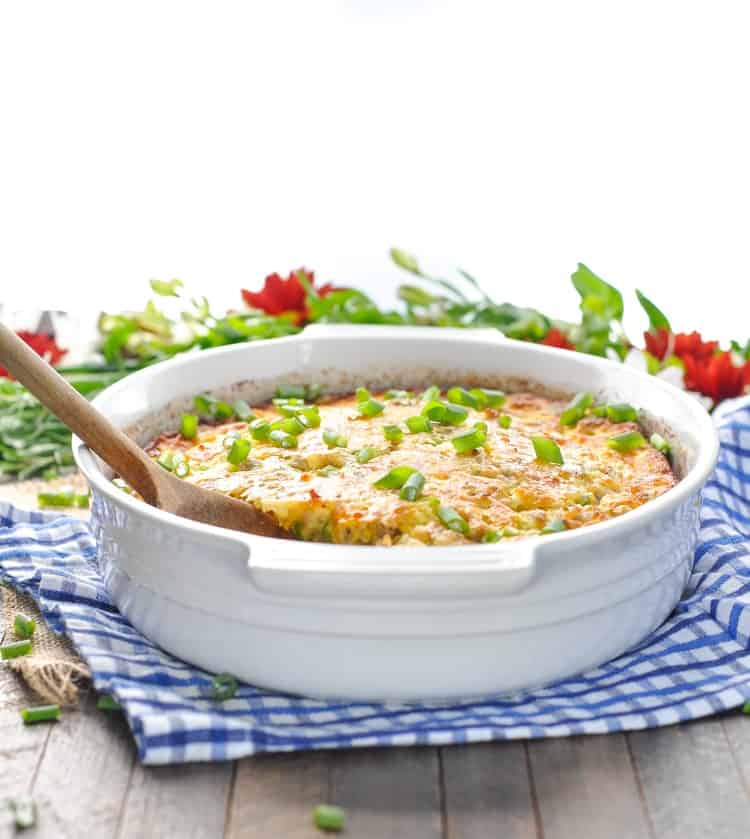 A side shot of an easy breakfast casserole in a white oval baking dish with a wooden spoon