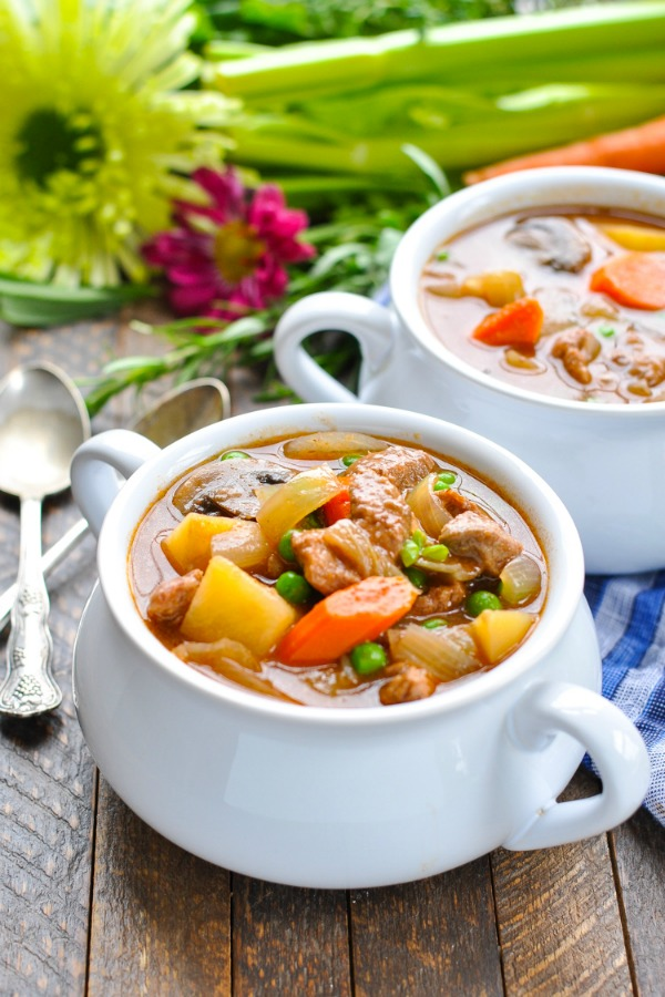 A beef stew in a white pot with carrots and potatoes