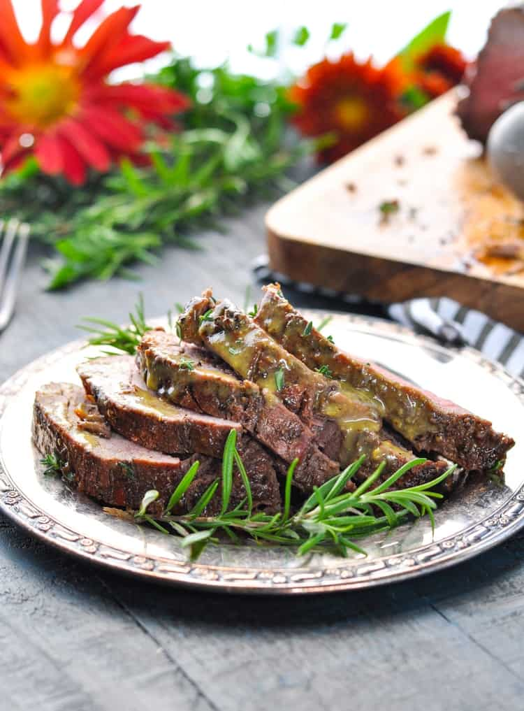 Sliced beef tenderloin on plate garnished with rosemary