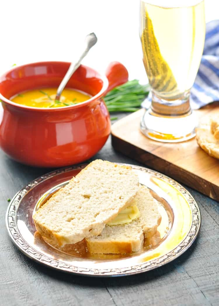 Slices of beer bread on a plate with a bowl of soup in the background