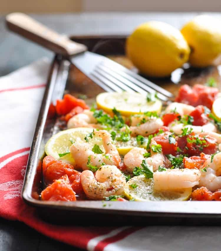 Baked shrimp on a sheet pan with lemons and tomatoes