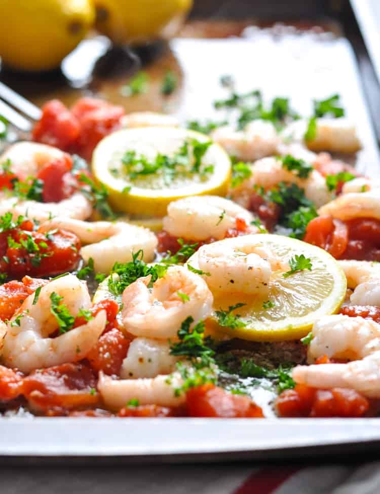 Baked shrimp on a baking sheet with tomatoes and lemons