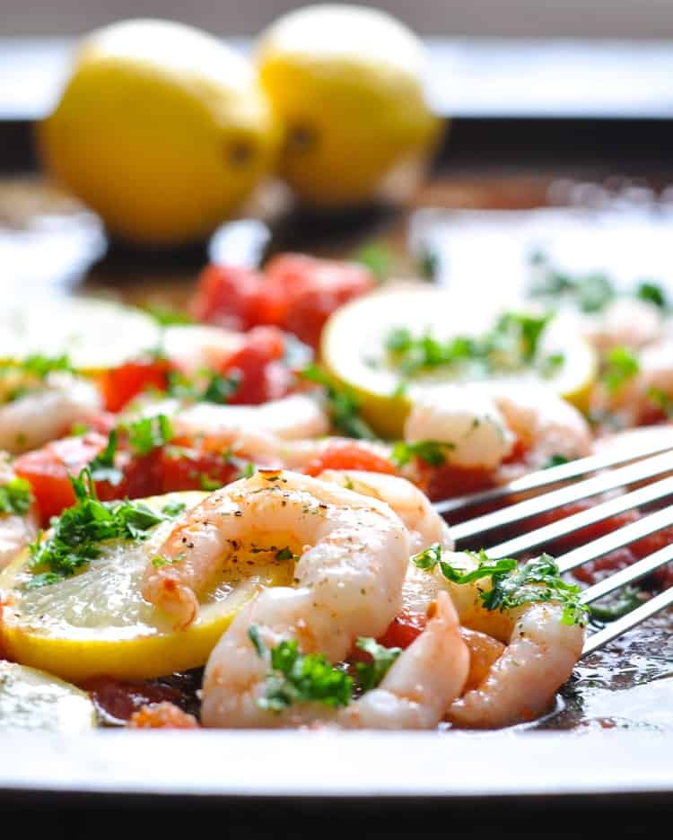 A close up of baked shrimp on a tray with lemons