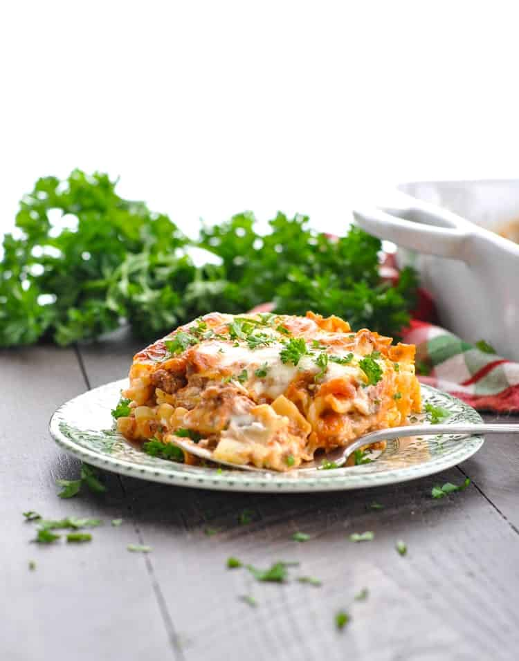 Piece of Italian lasagna on a plate with a fork