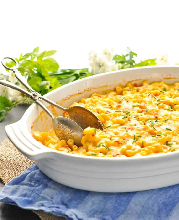 Dump and Bake mac and cheese with chicken in a white serving dish with tongs