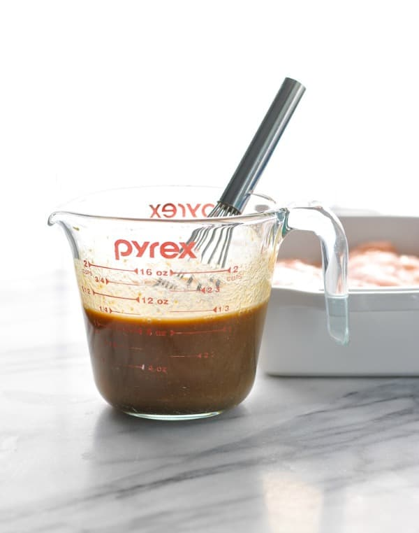 Maple balsamic sauce in a measuring cup with whisk