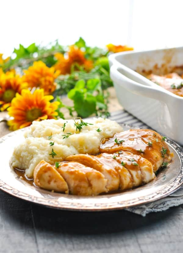 Sliced chicken with maple balsamic sauce on a silver plate