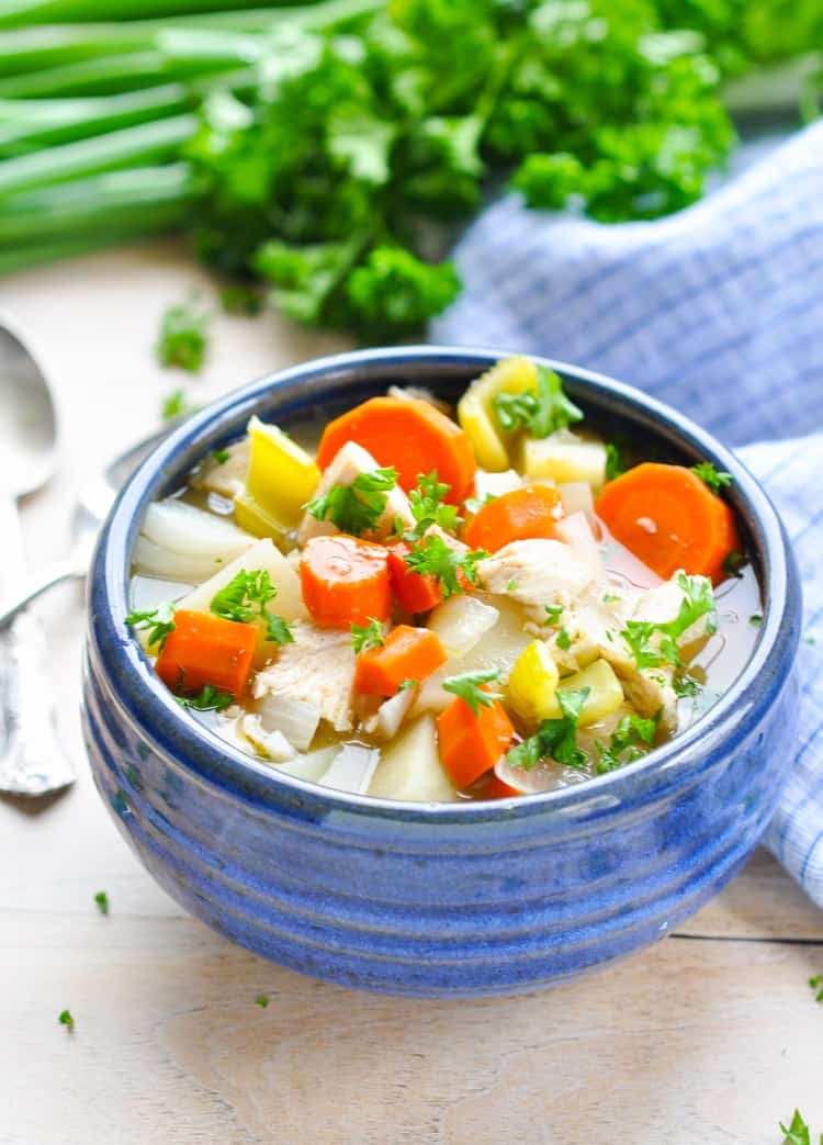 Blue bowl full of chicken stew with potatoes and garnished with fresh parsley