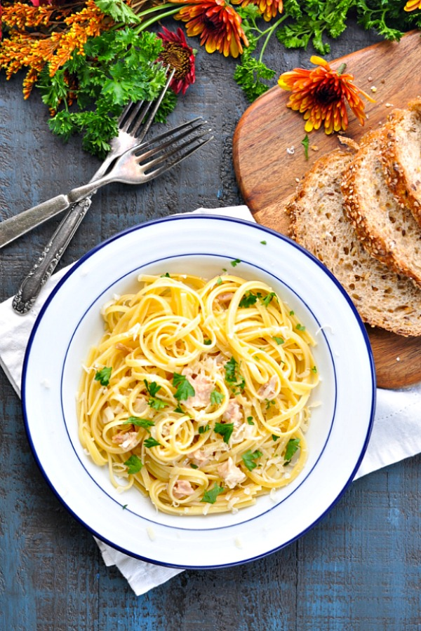 Bowl of pasta with clam sauce surrounded by flowers and herbs