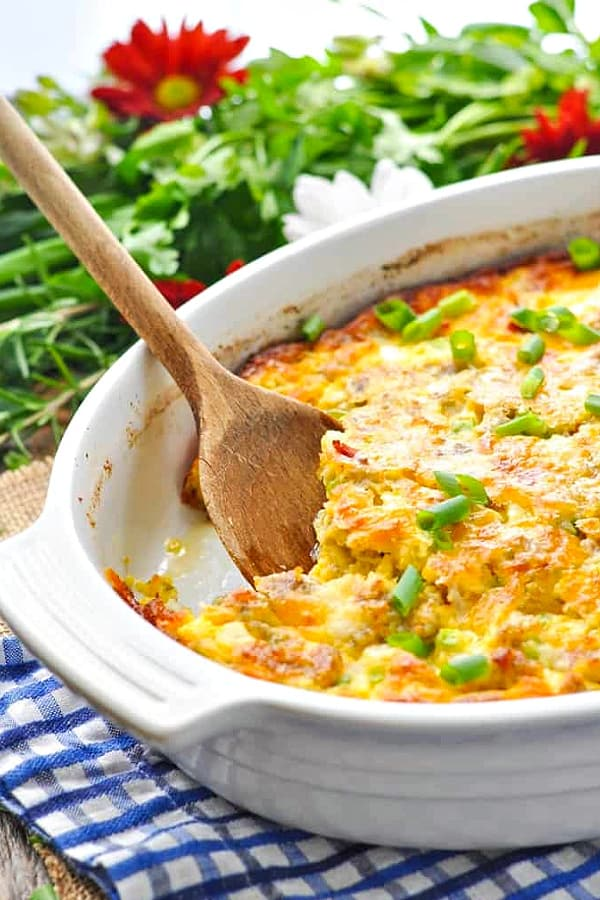 Bacon sausage and egg casserole in a white dish with wooden spoon