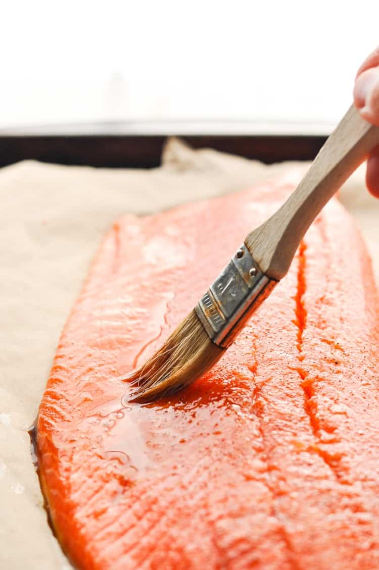 Basting a large piece of salmon with soy sauce