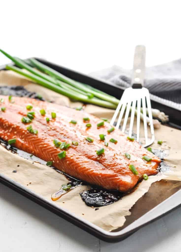 Baked salmon on a baking sheet garnished with green onions