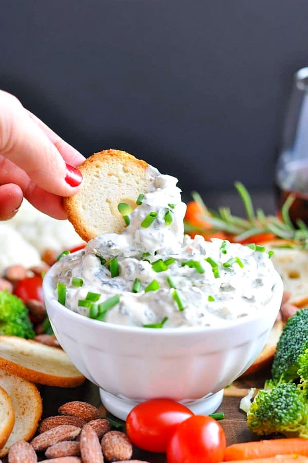 Hand dipping bagel chip in a white bowl of Knorr Spinach Dip