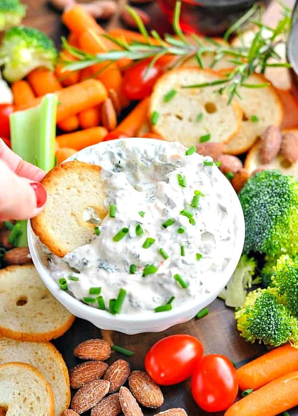 Overhead shot of creamy spinach dip in a white bowl on a veggie tray