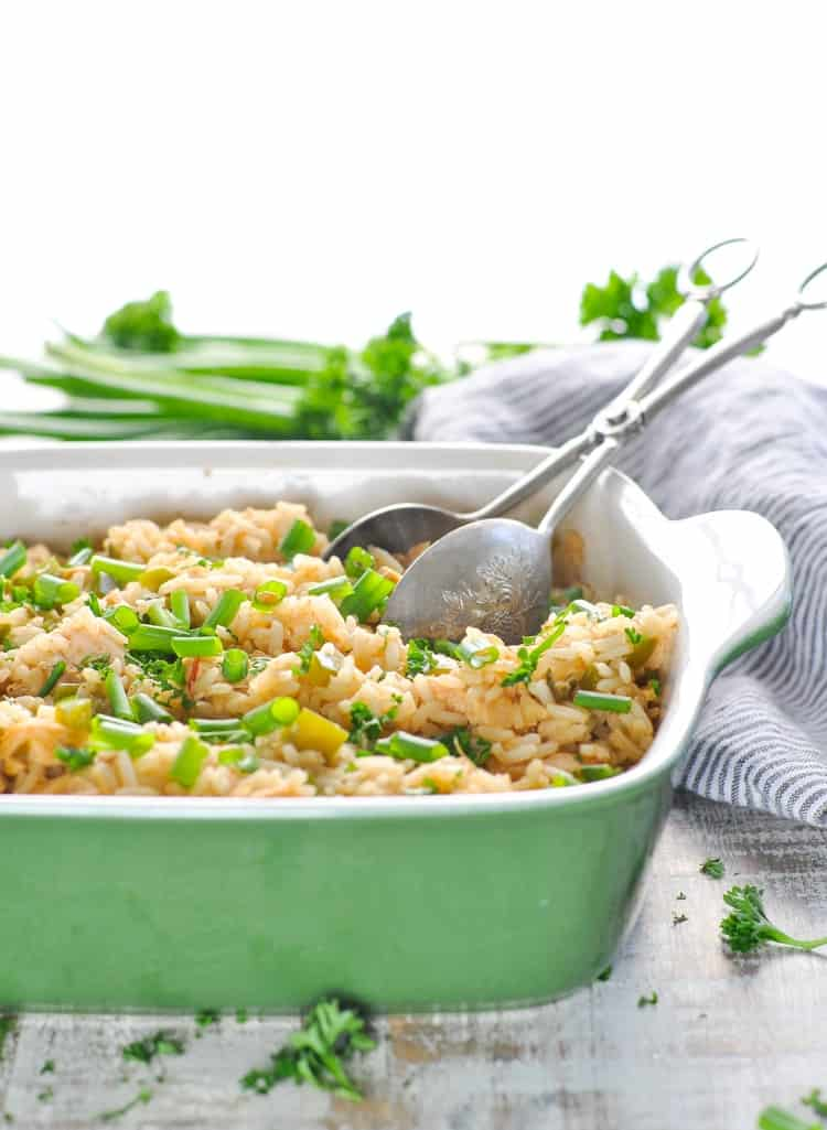Bright photo of chicken and dirty rice in a green casserole dish