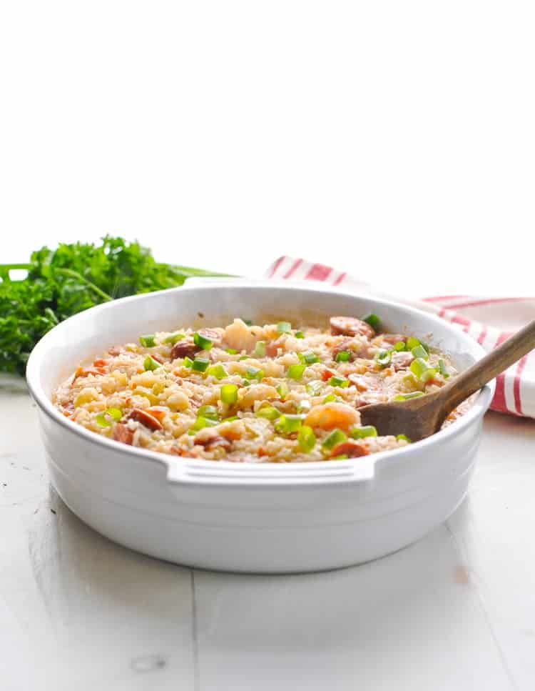 Jambalaya in a white serving dish with wooden spoon