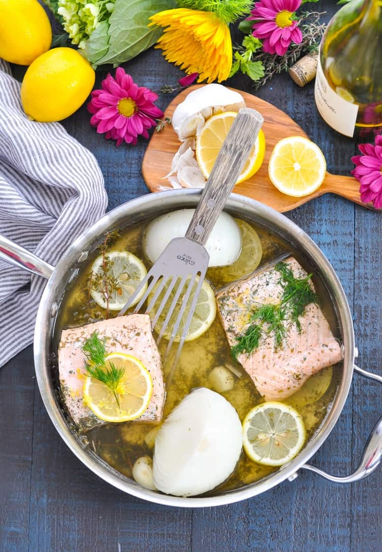 Overhead photo of two slices of Garlic and Herb Poached Salmon in the pan.