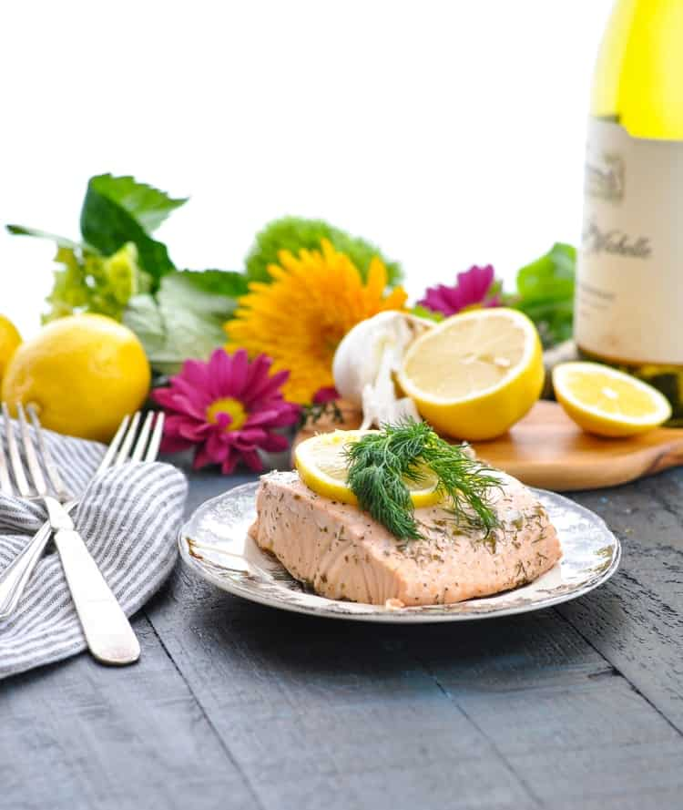 Poached salmon on a plate with lemon slices and fresh dill.