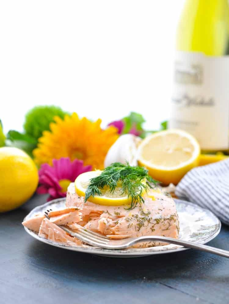 Bright beautiful photo of poached salmon on a plate with a fork and fresh flowers in the background