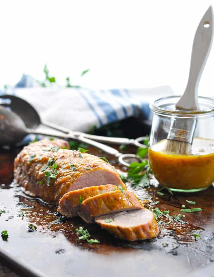 Bright vertical photograph of baked pork tenderloin on baking sheet.