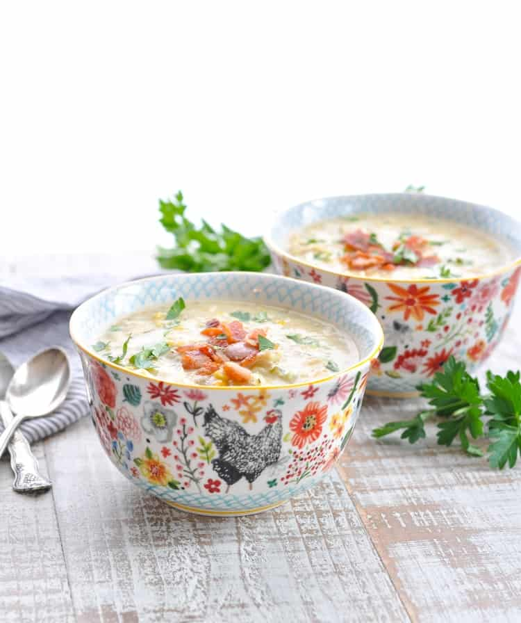 Two bowls of Crock Pot Chicken Corn Chowder topped with crispy bacon and fresh parsley.