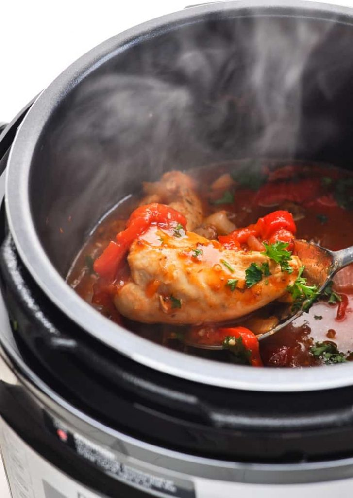 Italian chicken breast with sliced red peppers on a spoon in the Instant Pot