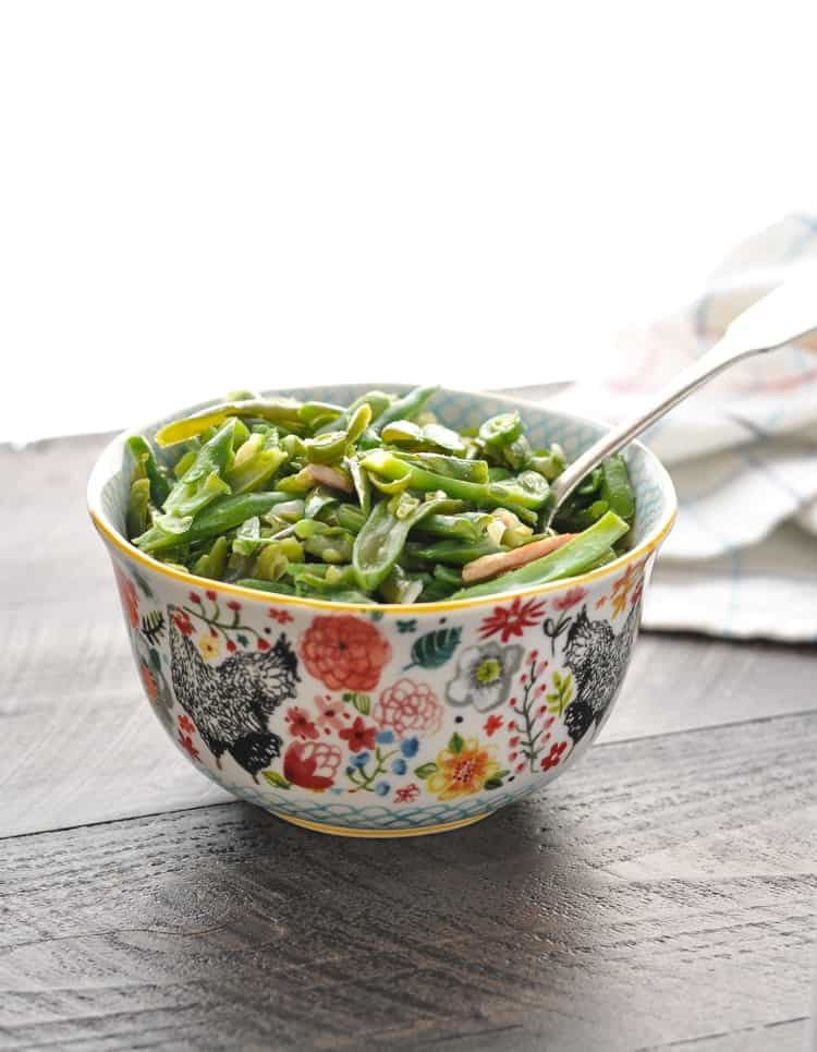 Vertical photograph of bowl of tender crock pot green beans with bacon and onion
