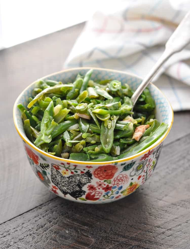 A bowl of slow cooker green beans with bacon sitting on a wooden surface