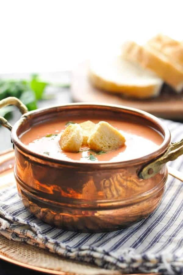 A copper bowl full of creamy tomato basil soup sitting on a striped dish towel