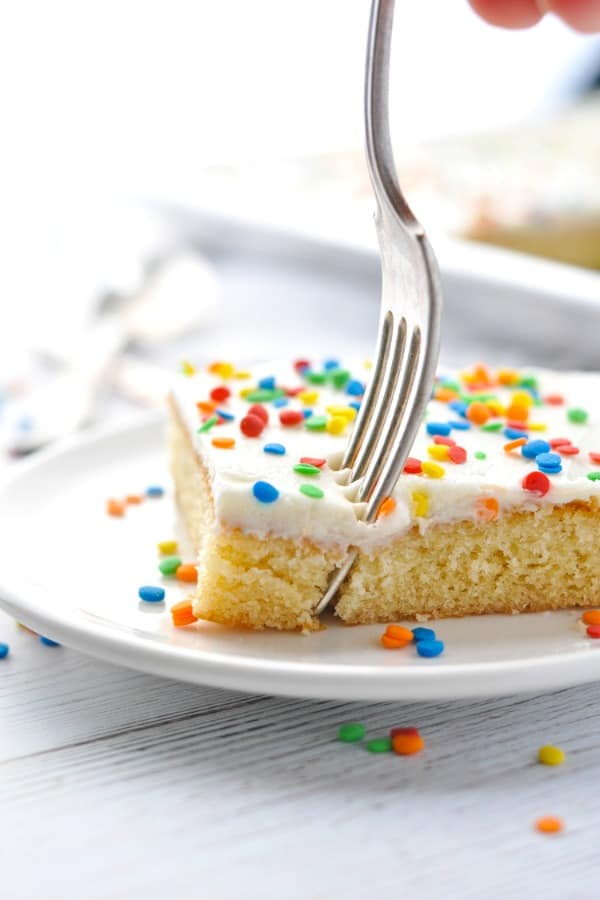 Fork digging in to slice of white texas sheet cake