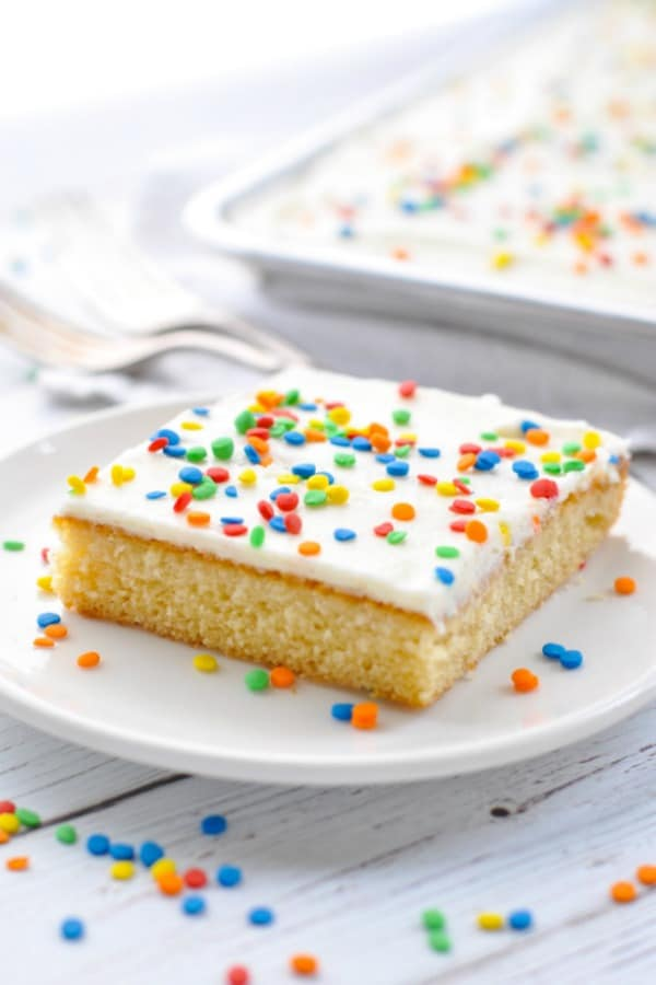 Slice of white texas sheet cake on a white plate with rainbow sprinkles