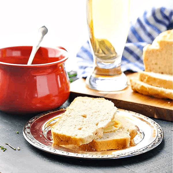 Square image of two slices of easy beer bread on a plate with beer and soup in the background
