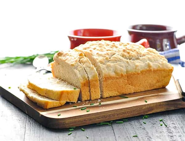 Horizontal shot of a sliced loaf of 3 ingredient beer bread made with no yeast on a wooden cutting board