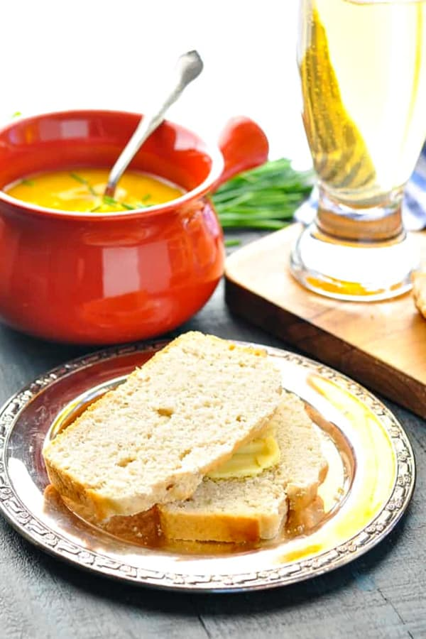 Two slices of easy beer bread on a plate served with soup
