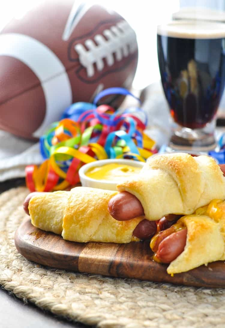 An image of easy appetizers on a tray -- hotdogs wrapped with cheese inside crescent rolls!